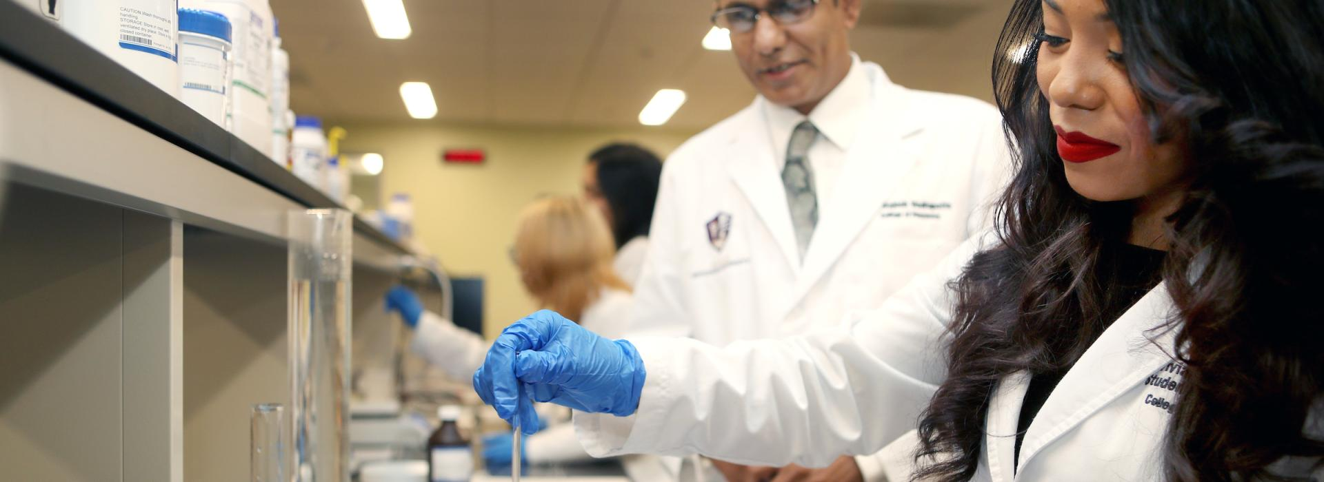 Pharmacy professor watches as female pharmacy student mixes compounds in a lab