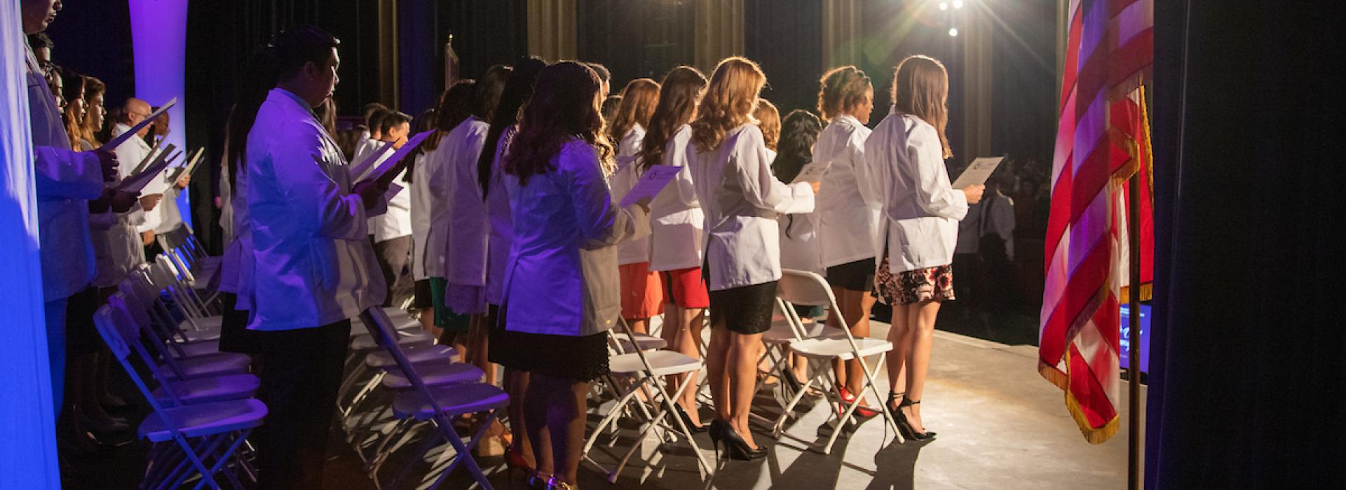 Students wearing white coats backstage